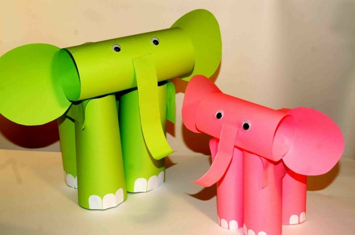 two elephants made from green and pink paper, folded in cylinders, decorated with white paper details and stick-on eyes