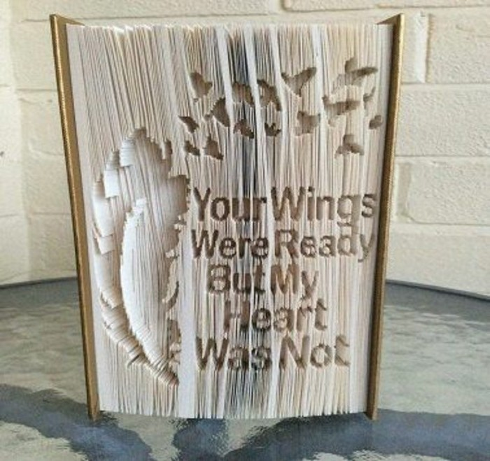 folded book art, thick closed book, with light brown hard covers, and a long message carved into its pages, along with a feather and some small bird shapes
