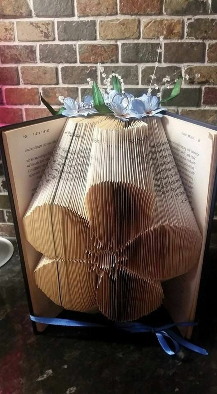 folded book art, flower made from folded pages, inside an open book, with hard black covers, tied with blue ribbon, and decorated with blue paper flowers