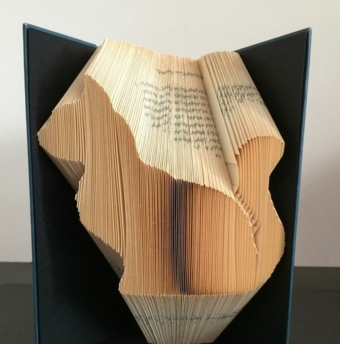 folded book art patterns, book with black hard covers, opened to display a cat shape, made from folded yellowy pages