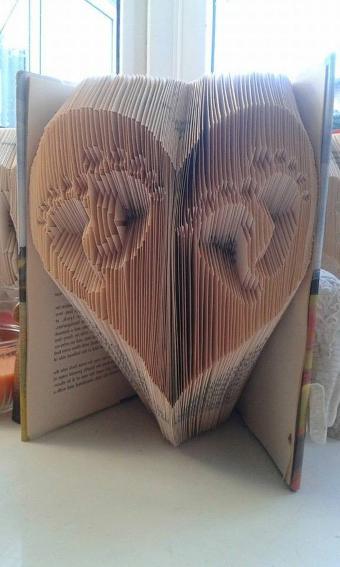 folded book art patterns, two sets of small baby foot prints, inside a heart shape, made from folded pages, inside an open book