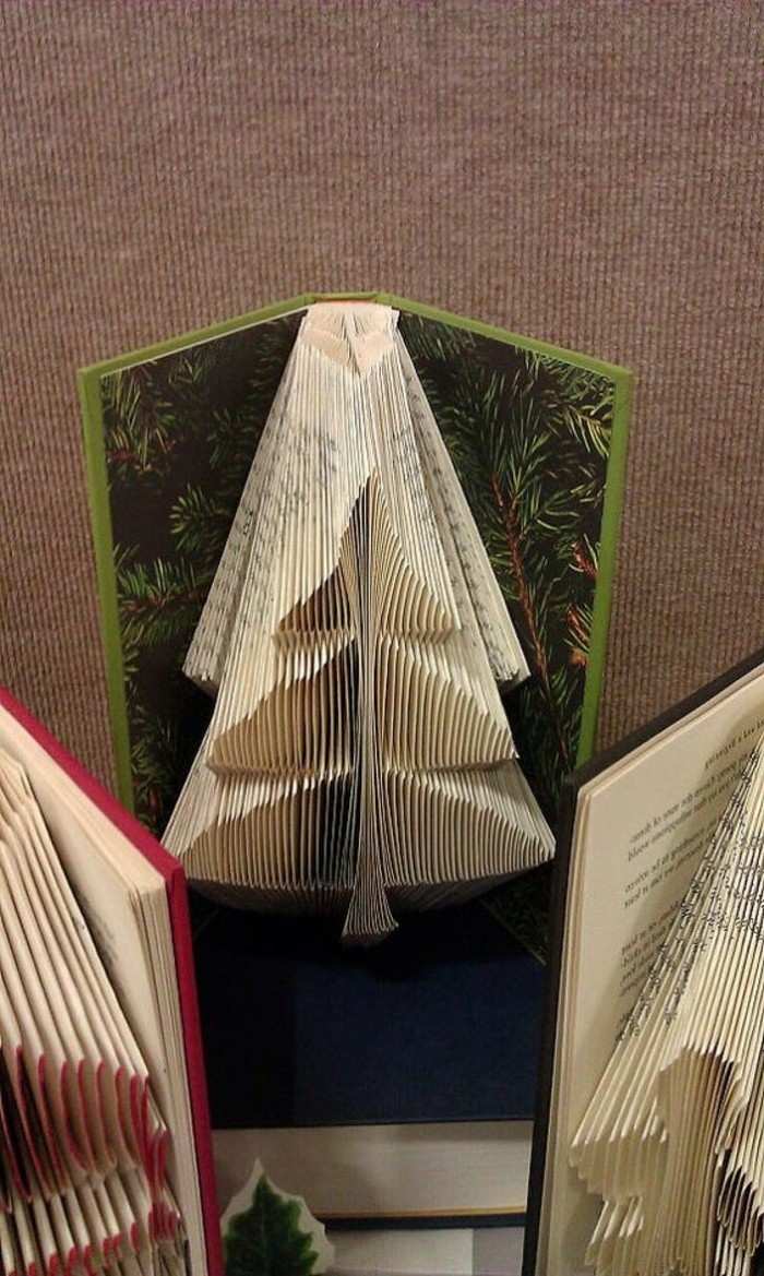 folded book art patterns, small Christmas tree, made from folded pages, inside an open book, with hard green covers, and pine tree pattern, more similar books nearby
