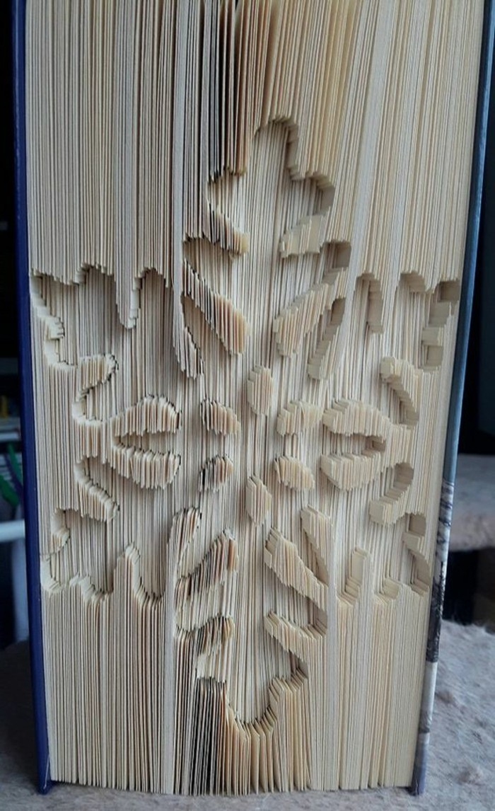 folded book art patterns, closed book with hard dark blue covers, and a snowflake shape, carved into its pages