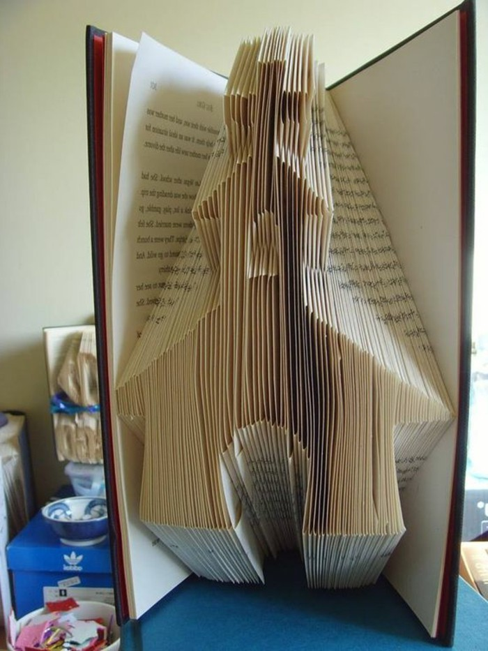 folded book patterns, a church shape, made from folded pages, inside a thin open book, with hard covers