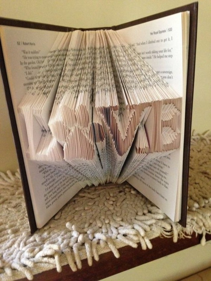 folded book patterns, the word love, with the o replaced by a paw print, made from many folded pages, inside an open book