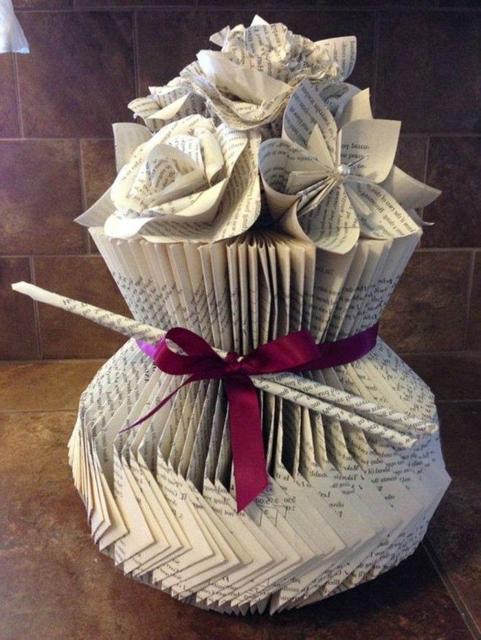 folded book patterns, a vase with flowers, all made from cut and folded book pages, decorated with a purple ribbon