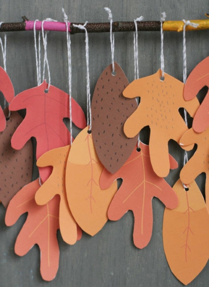 cool things to make at home, many orange and brown autumn leaves, made from paper, tied to a tree branch with white string