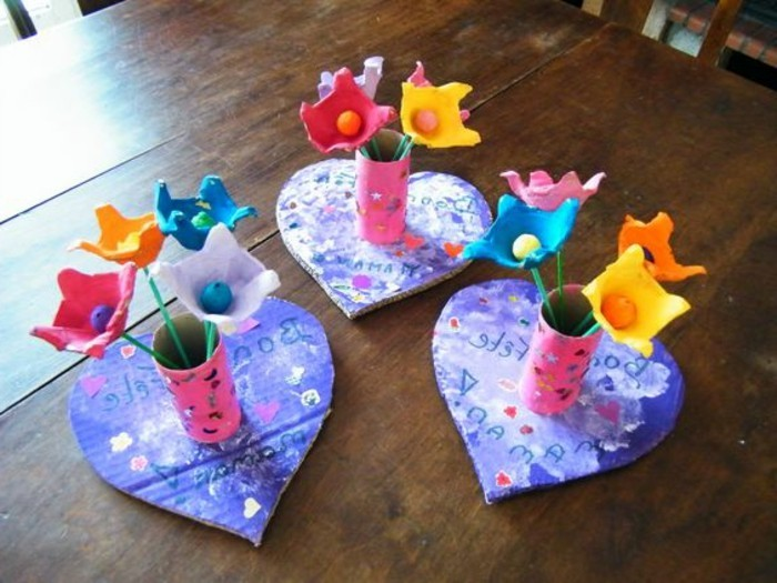 craft ideas for kids, three pink cardboard vases, placed on violet heart-shaped coasters, all decorated with scribbles, containing cardboard flowers in different colors