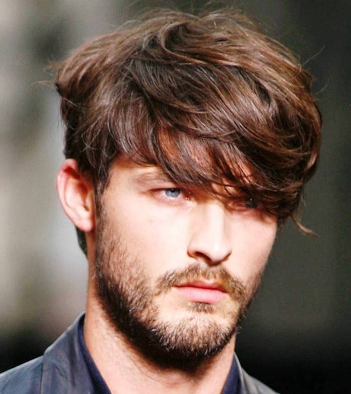 hairstyles for medium length hair, auburn haired man with long, wavy bangs partly covering his eyes, short beard and mustache