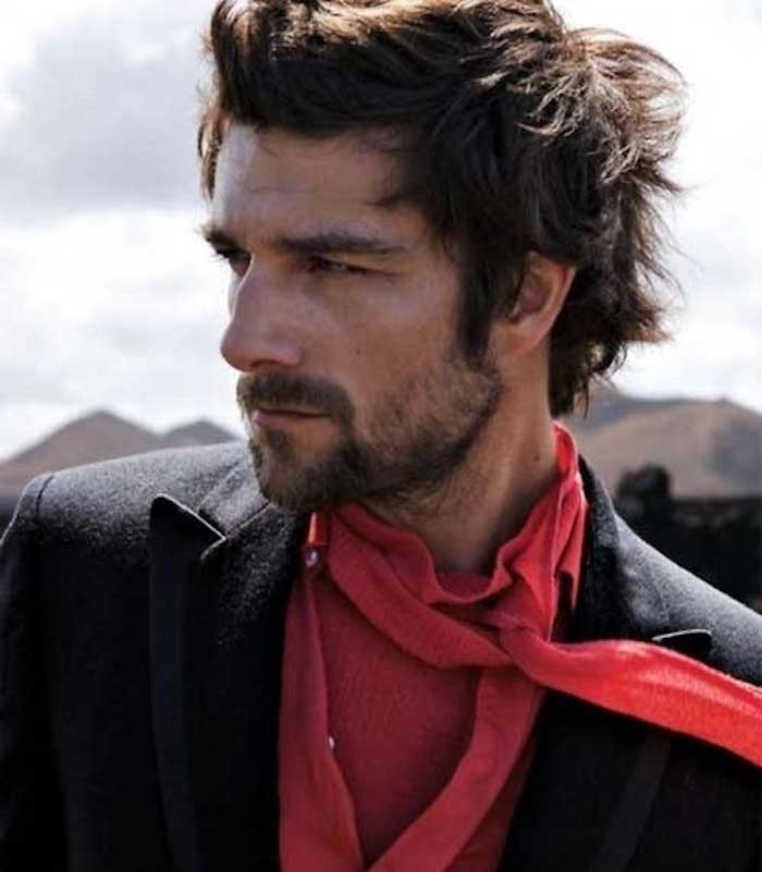 shoulder length hairstyles, man with shaggy messy hair, wearing black blazer, red shirt and scarf