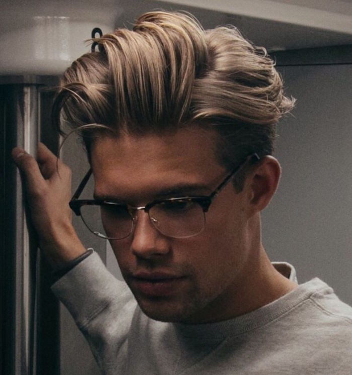 hairstyles for medium length hair, platinum blonde man with glasses, hair gelled up in messy pompadour style