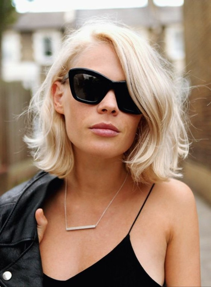 close up of a woman with blond, side parted wavy bob, wearing black sunglasses, and black strappy top, holding black leather jacket