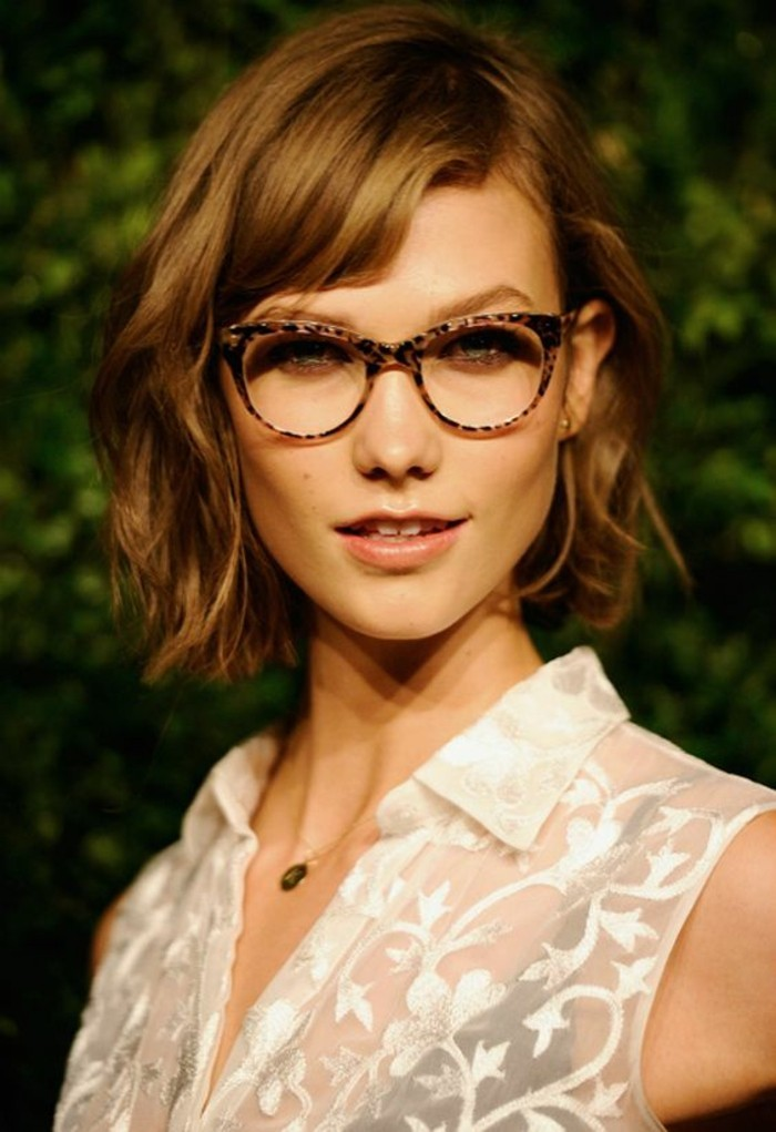 cute hairstyles, woman with wavy hazel bob and side bangs, wearing retro glasses, and white sheer sleeveless shirt