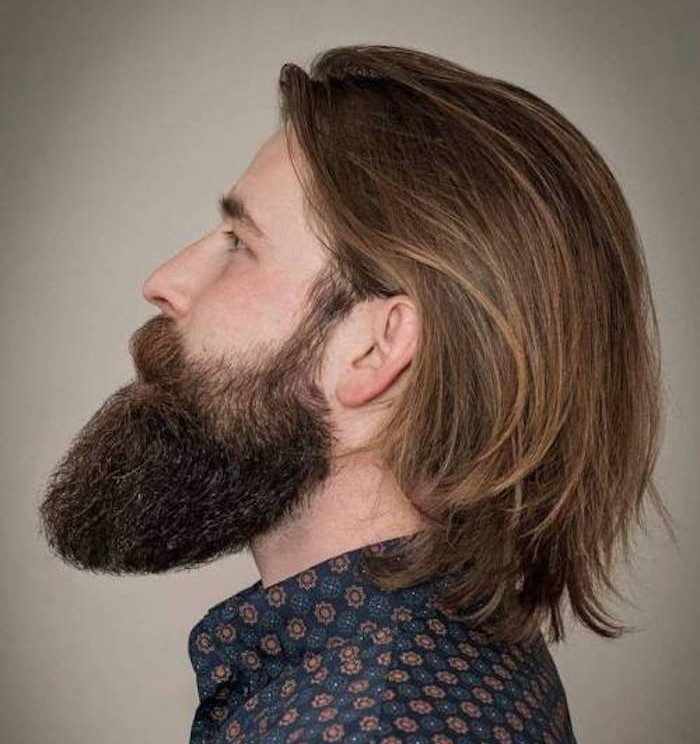 man with big beard, in profile and looking up, smooth dark blond hair tucked behind his ears, blue floral shirt