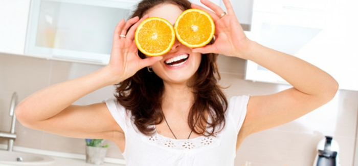 hazel eye color, laughing woman with wavy brown hair and white teeth, holding two orange slices in front of her eyes