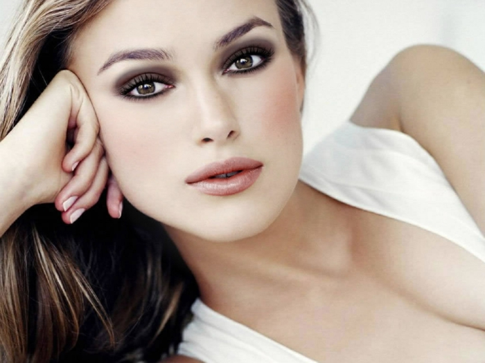 hazel eyes, close up of keira knightley, leaning on one arm, white top and brown hair, natural lipstick and smokey eye make up
