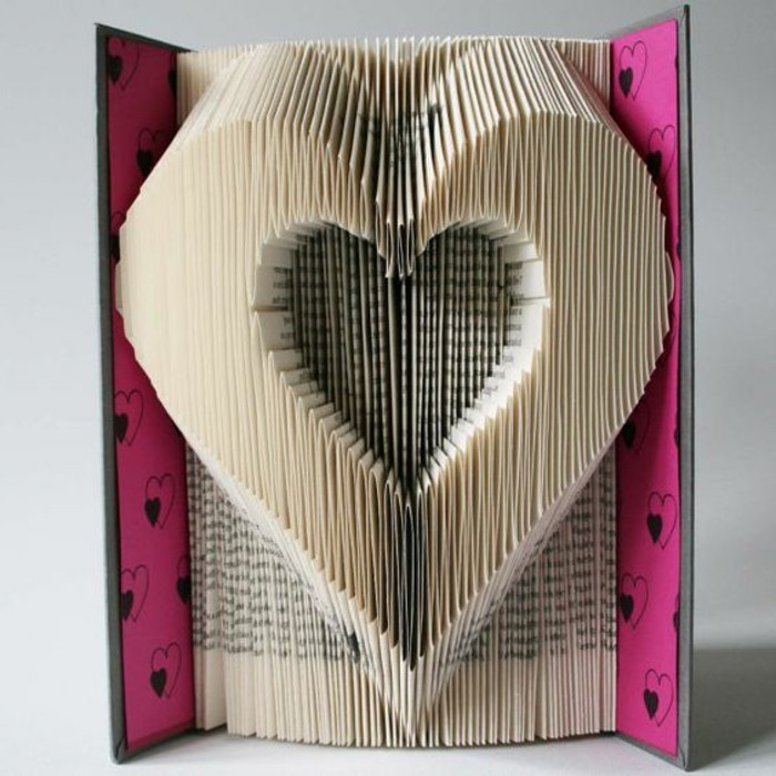 heart shape made from folded vintage pages, inside an open book, with pink and black hard covers