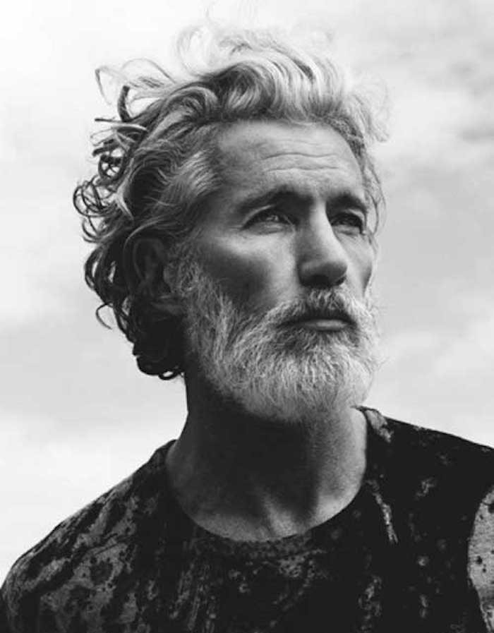 mid length hair, mature man with curly windswept white and grey hair, white beard and mustache