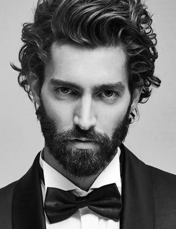 mid length hair, formally dressed man, in tuxedo and bowtie, curly dark hair swept to one side