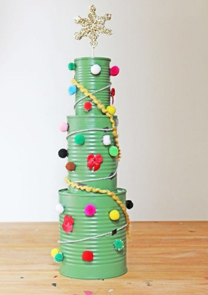 metal tin containers, christmas tree made from three differently sized cans painted in green, stacked on top of each other, decorated with colorful pom poms and tread, sparkling gold star on top