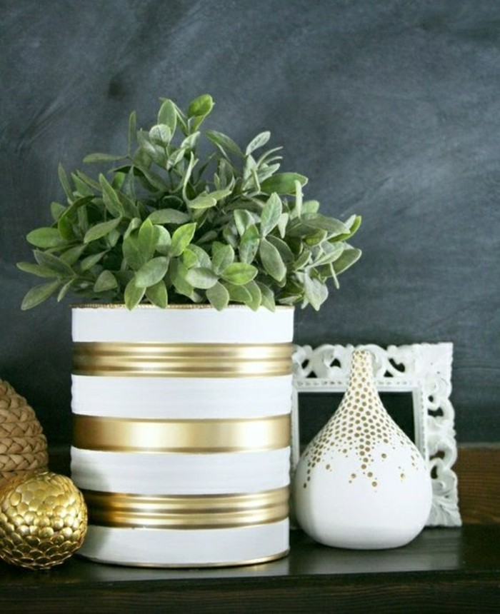 metal tin containers, a large tin colored with white and gold paint, containing green potted plant, white and gold decorations nearby