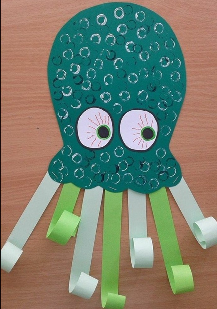 fun art projects, octopus made from dark green paper, decorated with pale green and blue paper tentacles, scales drawn in shiny marker