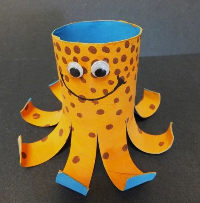 smiling octopus ornament, made from a toilet roll, painted in orange and blue, and decorated with marker and stuck-on eyes