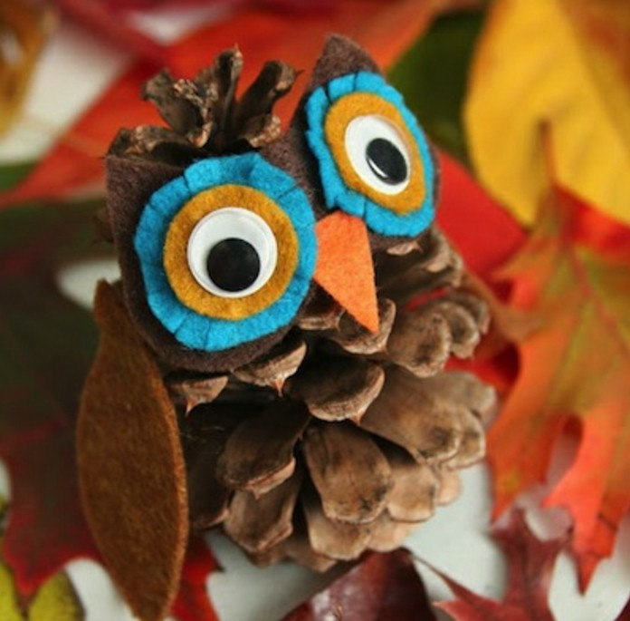 fun art projects, little owl ornament made from a pinecone, decorated with felt in different colors, with stick on eyes