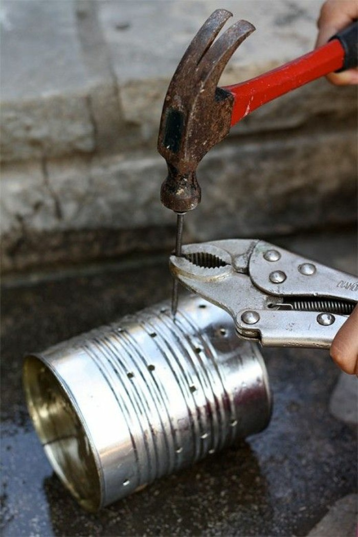 aluminum tins, person making holes into an aluminium can, using a nail, held with pliers, and a hammer