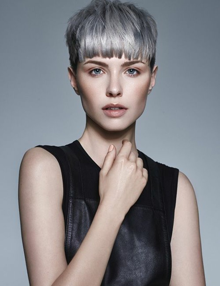 short hair cuts, slim woman with short light grey hair, layered cropped bangs, wearing black sleeveless leather top