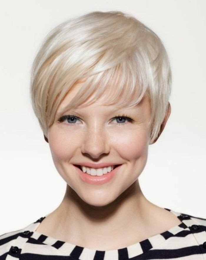 hairstyles for short hair, smiling woman with short platinum blonde pixie cut, blue eyes and natural-looking make up, wearing striped top