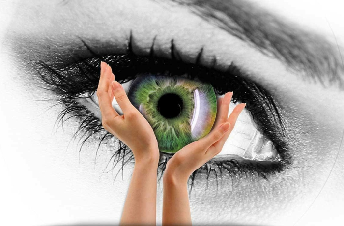 rarest eye color, collage featuring two female hands holding a green iris, on a black and white background, featuring a large eye