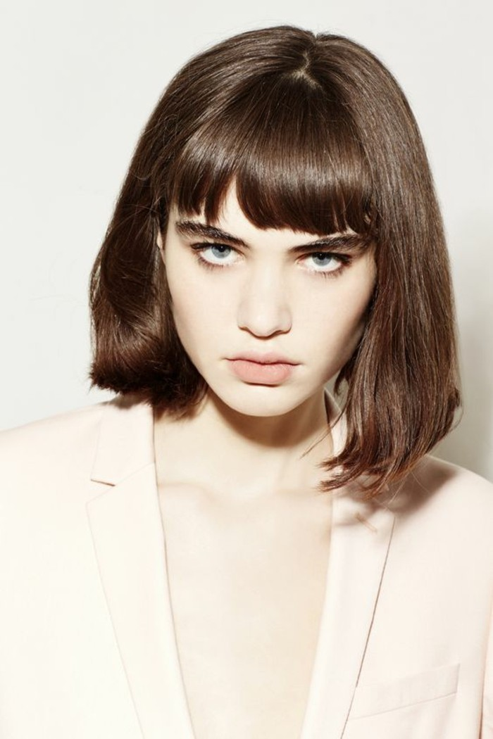 hairstyles for short hair, pale woman with brown shoulder-length hair and bangs, wearing white oversized blazer