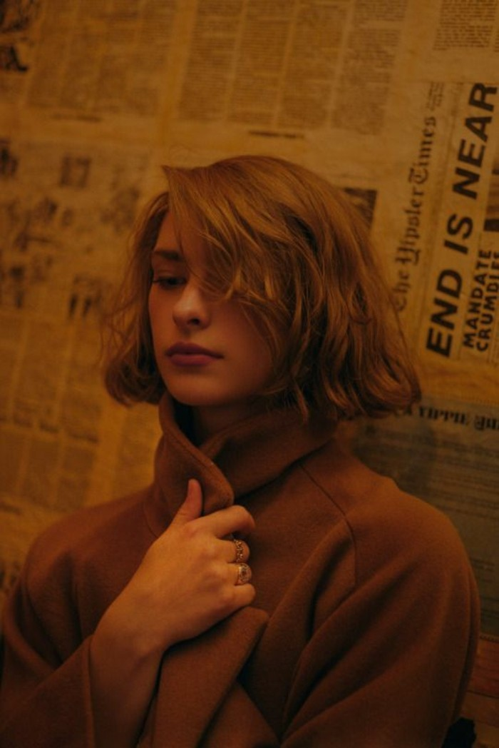 haircuts for women, woman with brown, side-parted wavy bob, wearing a brown woolen coat, and holding its lapel with one hand