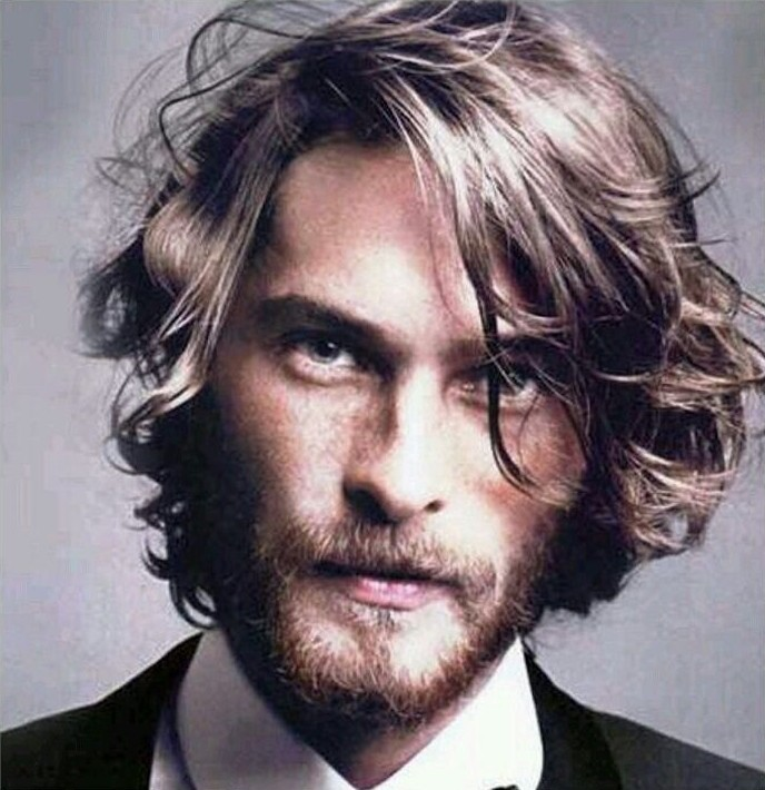 shoulder length hairstyles, close up of brunette man with curly and wavy hair, groomed mustache and beard