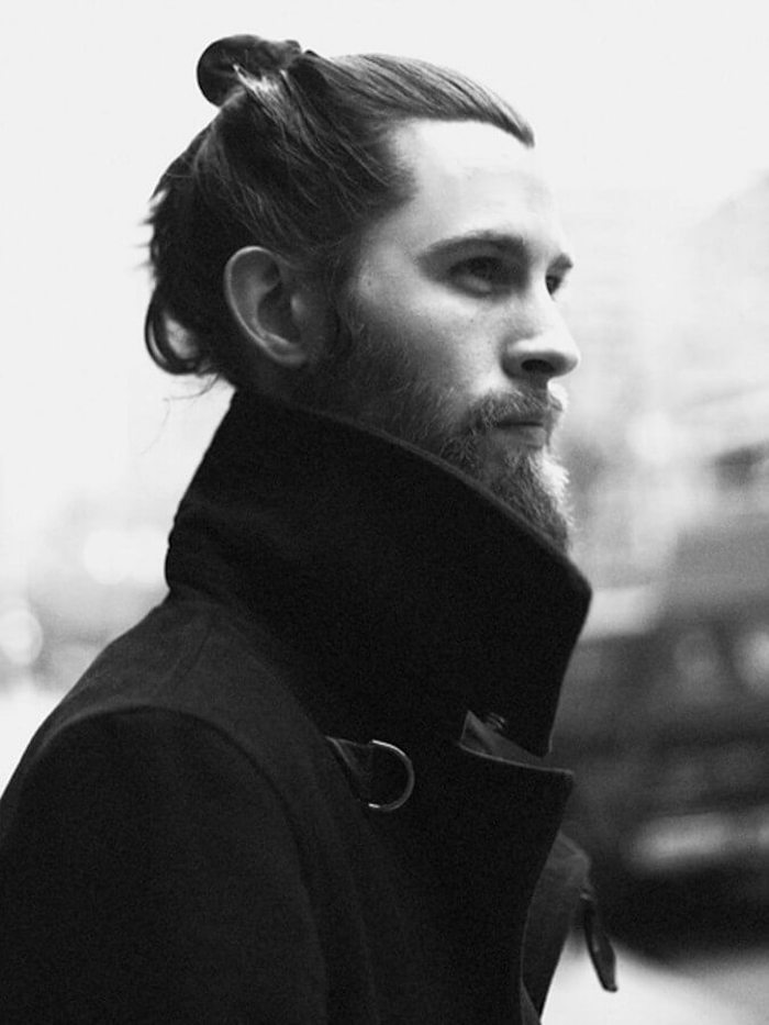 mid length hair, bearded man with man bun, wearing black coat with big collar, looking to the side