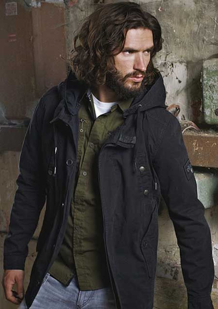 shoulder length hairstyles, man with curly brown hair, with mustache and beard, wearing dark parka over green shirt