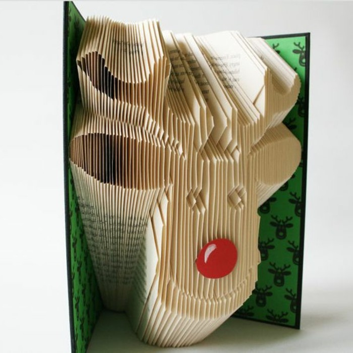 smiling reindeer head, created from folded pages, with red nose made, from round piece of paper, inside an open book, with black and green hard covers