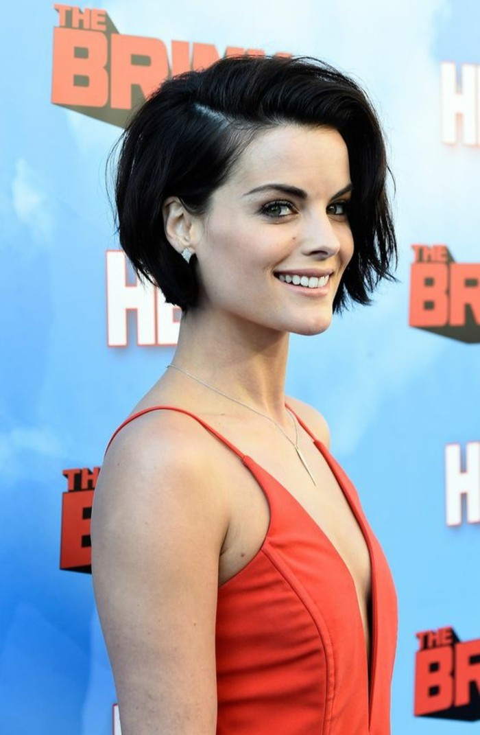 short haircuts, smiling black-haired woman, with side-swept bob and red strappy dress