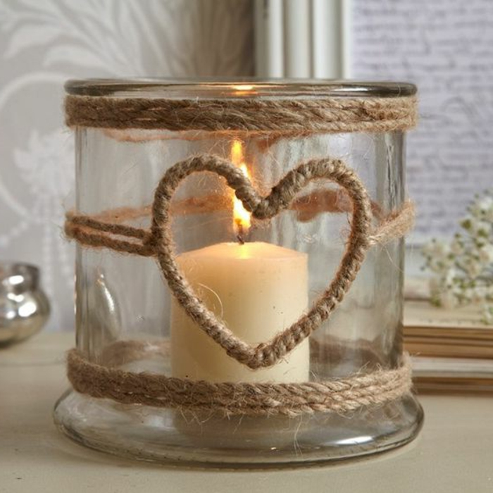 summer crafts, big jar decorated with burlap ropes, with heart-shape detail, containing one lit candle