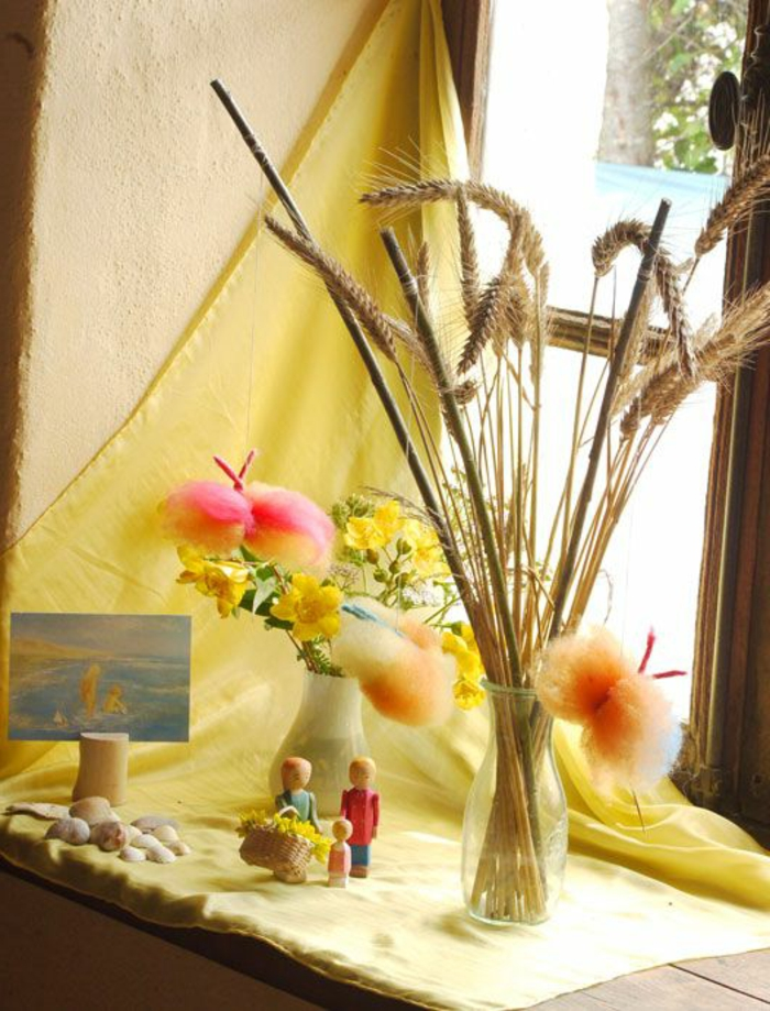 summer crafts, window settee decorated with bright yellow fabric, with two vases containing wheat stalks, yellow flowers and colorful woolen decorations, seashells and pebbles, a postcard and a small doll family nearby