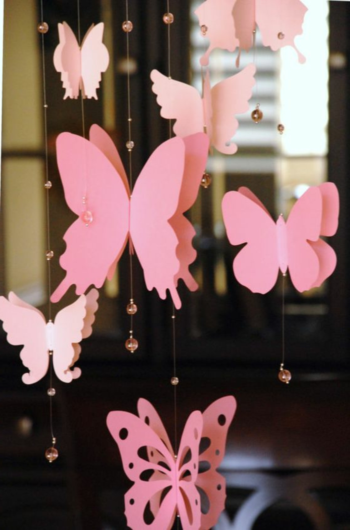 diys to do with friends, decoration made from differently shaped, pink butterfly paper cutouts, tied to thin strings, decorated with tiny clear pink beads