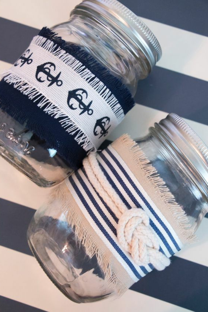 summer crafts, two mason jars, with screw lids, decorated with white and navy blue fabric, with nautical patterns, and rope tied in sailor's knot