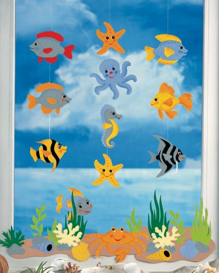 easy fun diys, decoration made from several paper cutouts, shaped like cartoon-fish and sea animals, hanging from white peaces of thread, cartoon underwater picture in background