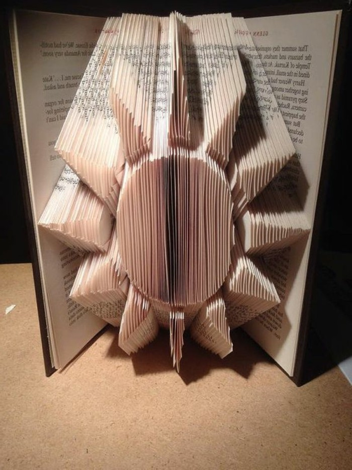 sun shape made from folded pages, inside an open book, with dark hard covers