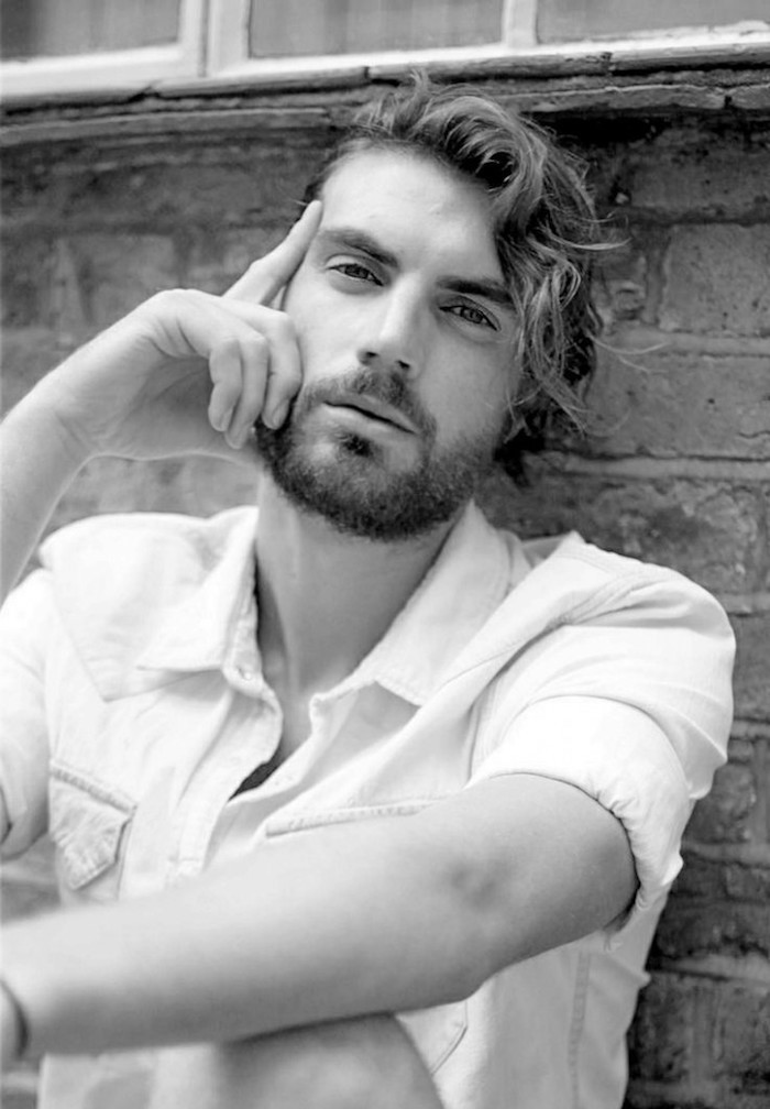 mid length hair, man leaning on brick wall, curly hair parted to one side, stubbly beard and white shirt