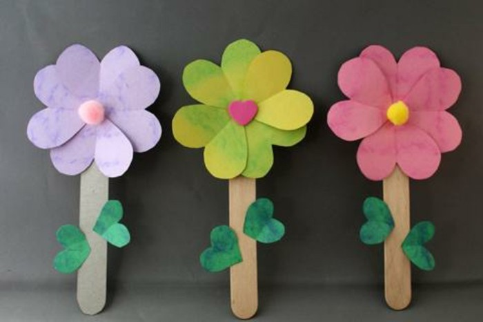 diy art projects, three flowers made of paper in pale violet, green and red, attached to stalks made from ice cream sticks, with small green paper leaves