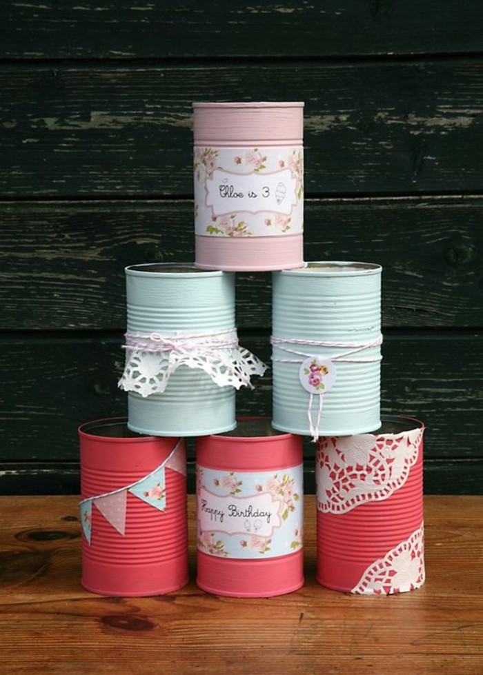 aluminum tins, six cans stacked in a pyramid, colored in salmon pink, light blue and pastel pink, decorated with string, floral paper and white doilies