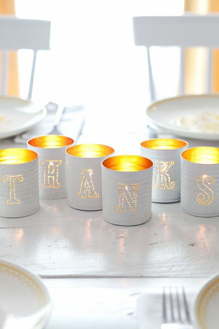 six luminaries made from cans, painted white and containing lit candles, with holes shaping different letters on each can, placed so as to form the word thanks