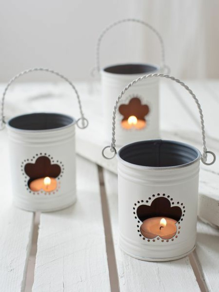 tin cans for crafts, three tin cans painted white, whit twisted wire handles, and flower shaped holes, containing small lit candles
